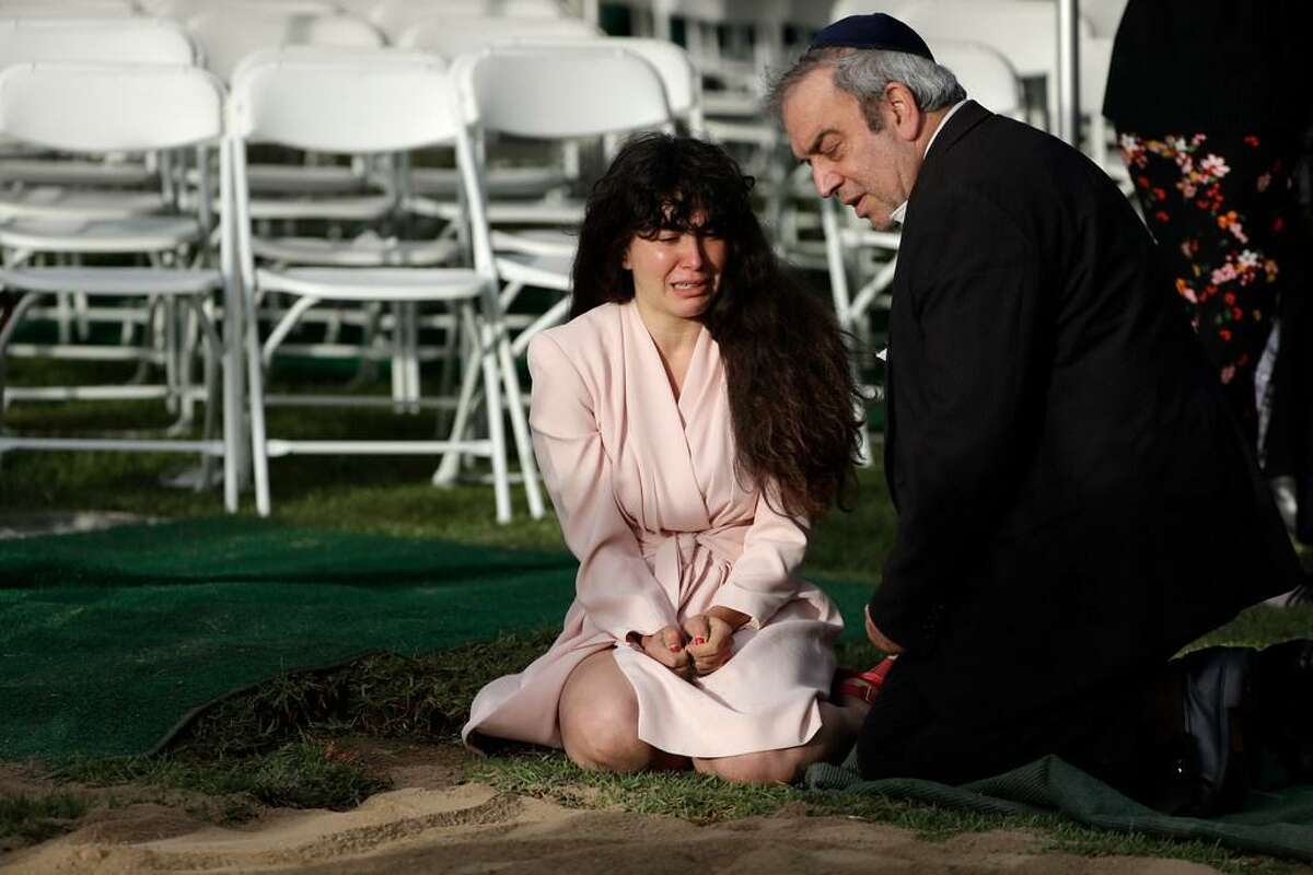 Hannah Kaye, the daughter of shooting victim Lori Kaye, sits alongside her father, Howard Kaye, at her mother's grave during funeral services in San Diego last year. Lori Kaye was killed when a man opened fire in April 2019 inside a San Diego synagogue as worshipers celebrated the last day of a major Jewish holiday.