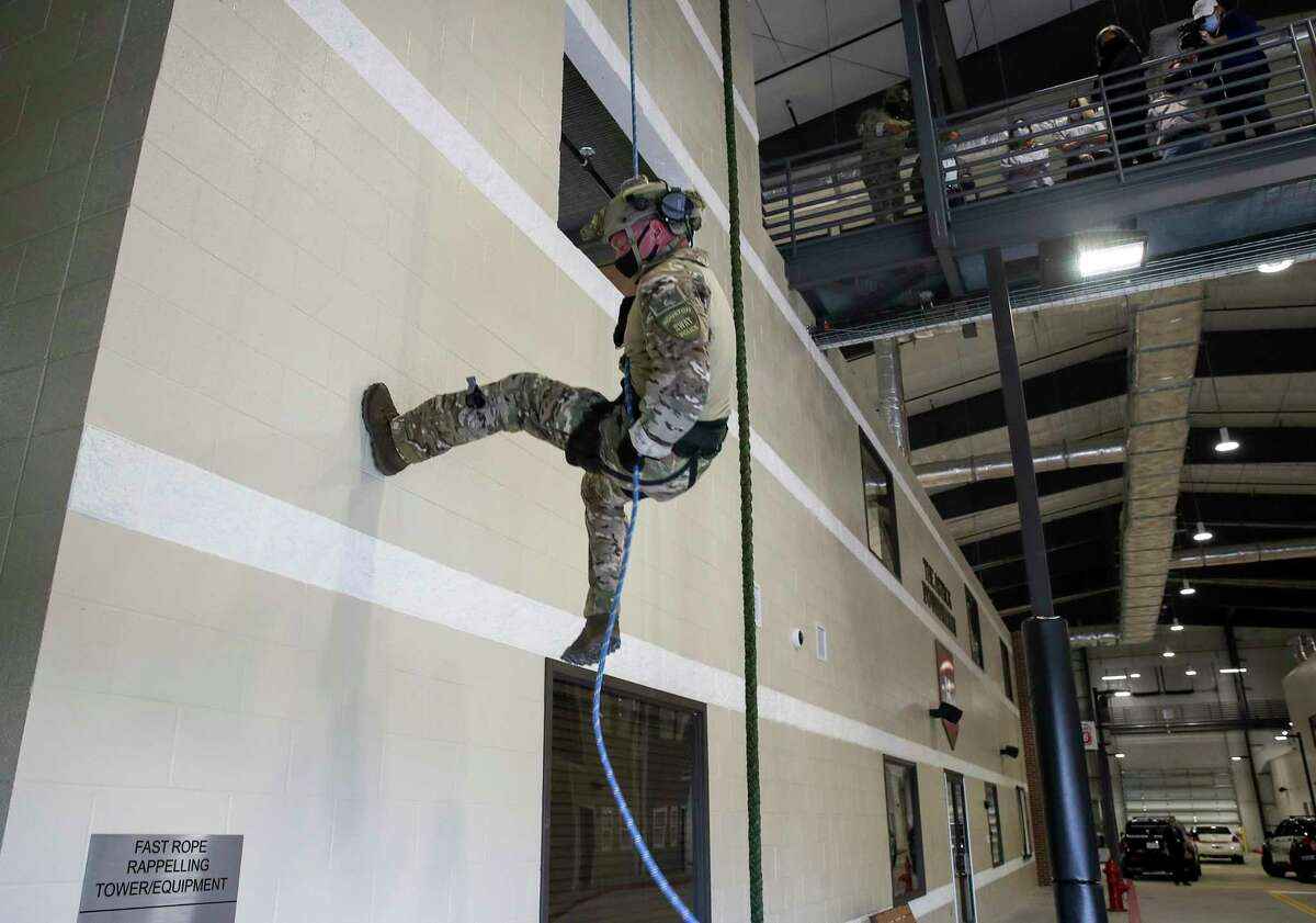 Houston Police Department Senior Officer Gary Heath, a member of the department's SWAT team, demonstrates how to rappel down a building during a ceremony to unveil a new HPD training center Thursday, Nov. 19, 2020, at the Tilman Fertitta Family Tactical Training Center in Houston.