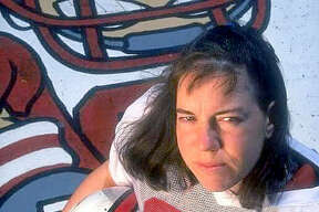 Kathy Klope poses on the University of Louisville logo on the football field in 1995. Klope, a graduate of Alton High, played soccer four seasons at Louisville as a goalie. Using a fifth year as a graduate student, she tried out for the football team and made it, although she never got to kick in a game. She was the first women to make am NCAA Division I football roster and the first to dress for a game.