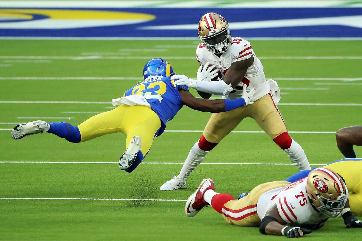 INGLEWOOD, CALIFORNIA - NOVEMBER 29: Jordan Fuller #32 of the Los Angeles Rams attempts to tackle Deebo Samuel #19 of the San Francisco 49ers during the first half at SoFi Stadium on November 29, 2020 in Inglewood, California. (Photo by Katelyn Mulcahy/Getty Images)