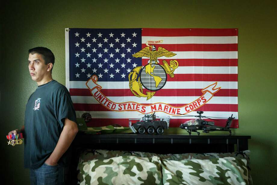 Retired Marine Sgt. Marty Gonzalez was awarded three Purple Hearts and earned two Bronze Stars during his military service, shown in his son's bedroom on Jan. 22, 2014, in Houston. Gonzalez died unexpectedly on Saturday. Photo: Michael Paulsen, Staff / Houston Chronicle / © 2014 Houston Chronicle