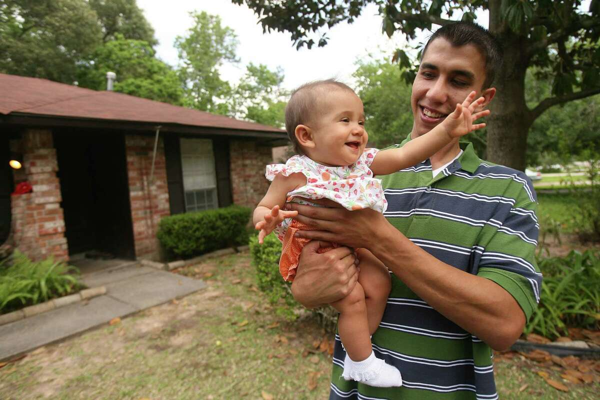 Marty Gonzalez, 29, carries daughter Kaylen Gonzalez, 9 months, outside his father Tomas Gonzalez, retired U.S. Army Spc. E4, home on April 26, 2009 in Spring.