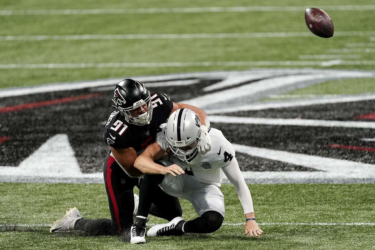 Falcons defensive tackle Jacob Tuioti-Mariner (91)hits Las Vegas Raiders quarterback Derek Carr (4) for a fumble during the first half of an NFL football game, Sunday, Nov. 29, 2020, in Atlanta. The Atlanta Falcons recovered the ball. (AP Photo/John Bazemore)
