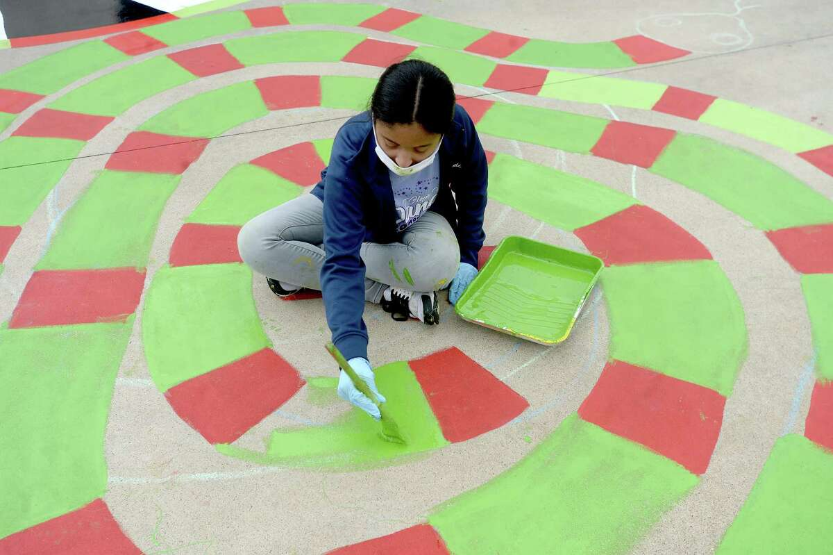 West Brook Art Club member Kaydi Daigre finishes painting artwork on the playground at Blanchette Elementary School Tuesday morning. Members of the West Brook Art Club took on the volunteer work during their Thanksgiving break, beginning the project Saturday. Photo taken Tuesday, November 24, 2020 Kim Brent/The Enterprise