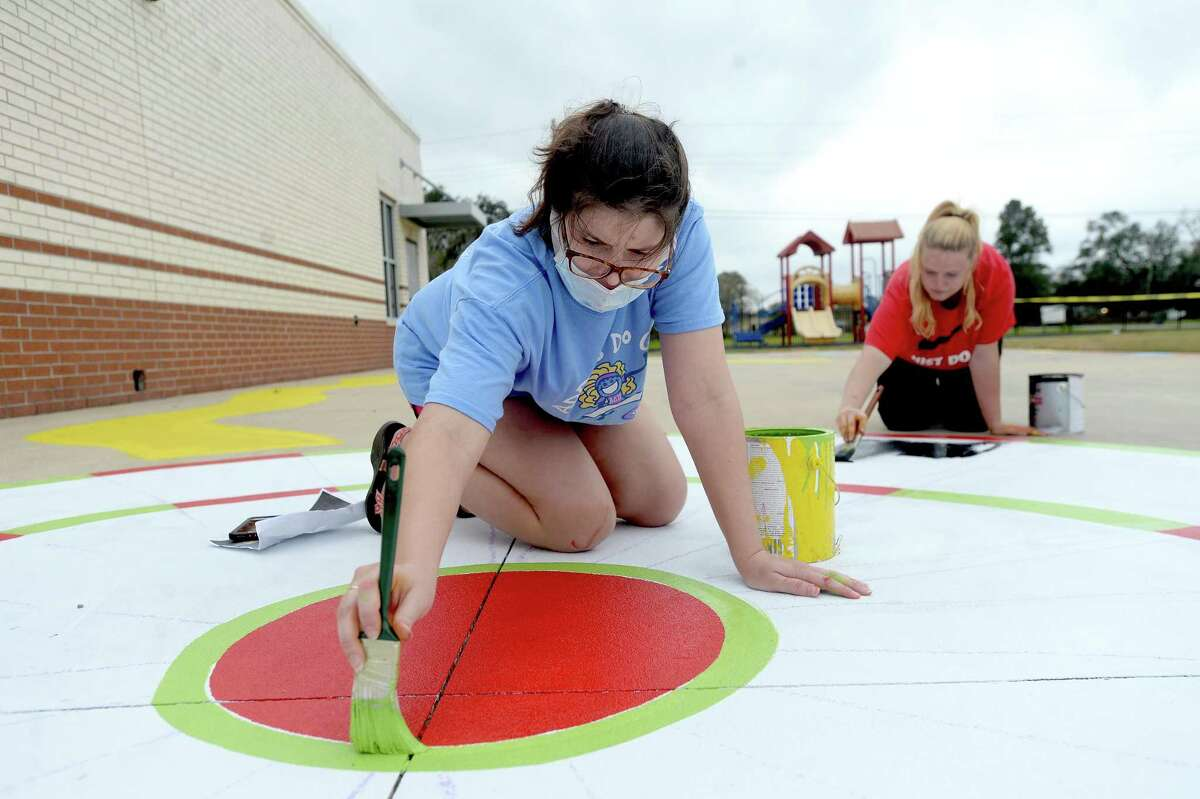 West Brook art teacher Loni Lilley (right) and Blanchette art teacher Stephanie Messina continue painting artwork on the playground at Blanchette Elementary School Tuesday morning. Members of Lilley's West Brook Art Club took on the volunteer work during their Thanksgiving break, beginning the project Saturday. Photo taken Tuesday, November 24, 2020 Kim Brent/The Enterprise