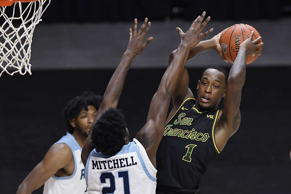 San Francisco's Jamaree Bouyea, right, looks to pass as Rhode Island's Makhi Mitchell, left, defends in the second half of an NCAA college basketball game, Sunday, Nov. 29, 2020, in Uncasville, Conn. (AP Photo/Jessica Hill)