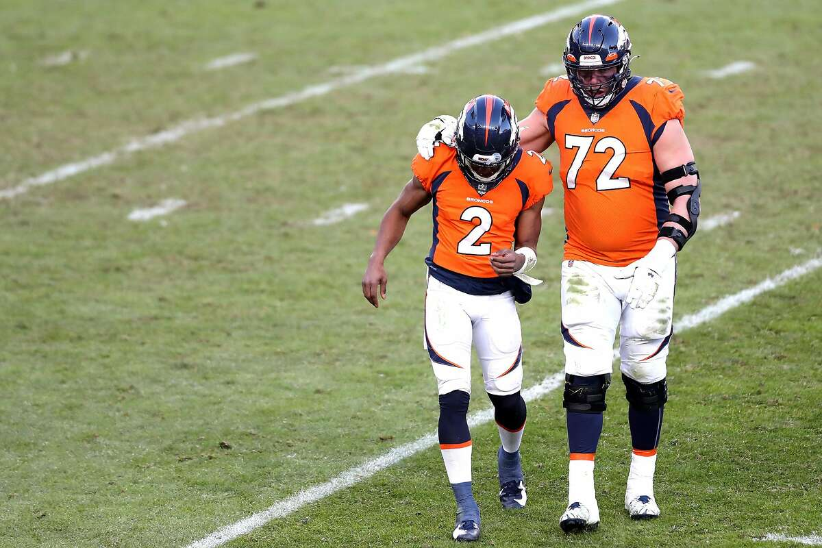 Broncos quarterback Kendall Hinton (2), normally a wide receiver, walks off the field with tackle Garett Bolles following an interception during the third quarter against the Saints.