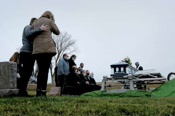 Dean Cynor, sitting, hands folded in center, attends the funeral for his mother at the Bohemian National Cemetery in Cadott, Wis., on Wednesday, Nov. 25, 2020. While he was being treated at the Mayo Clinic, his mother was admitted to the hospital two floors above him with what turned out to be a fatal case of covid-19.