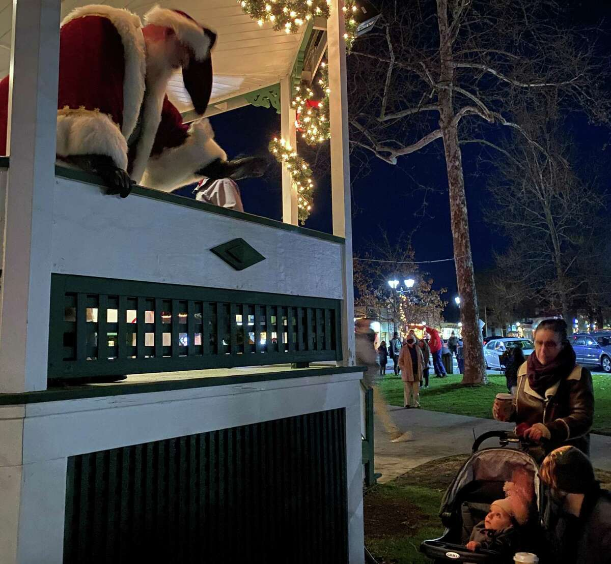 Santa Claus offers a wave to Alex Inch, 1, and his parents as they pass by the bandstand at the conclusion of the ceremony.