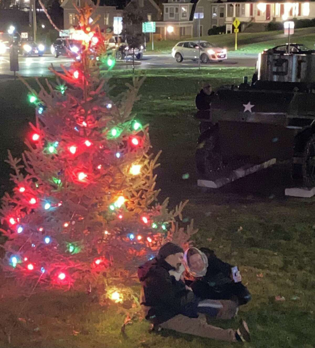 A young family takes their photo in front of one of the lighted trees.