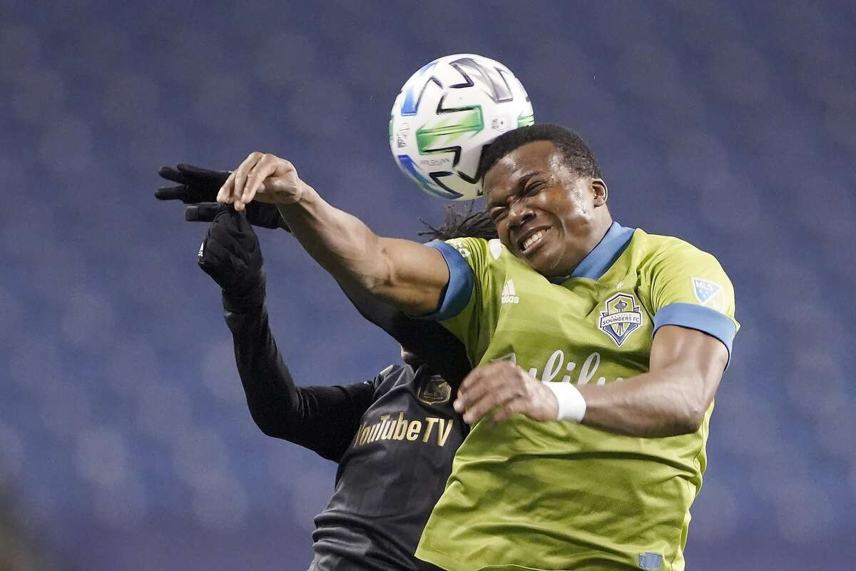 Seattle Sounders defender Nouhou, right, and Los Angeles FC forward Latif Blessing leap to head the ball ball during the second half of an MLS playoff soccer match Tuesday, Nov. 24, 2020, in Seattle. (AP Photo/Ted S. Warren)