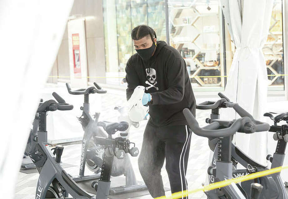 A worker sprays exercise bicycles with a disinfectant. Photo: Noam Galai | Getty Images