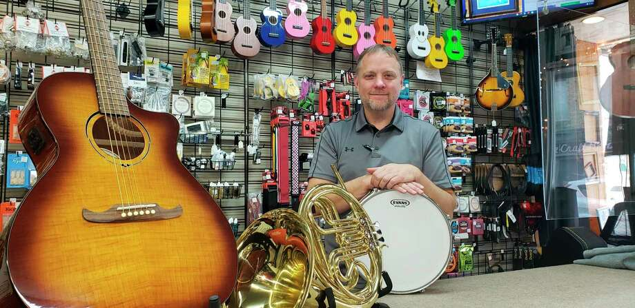 Owner Jason Parmenter poses among the many instruments for sale at Quad N Productions at the Frame Shoppe in downtown Caro. (Submitted Photo)