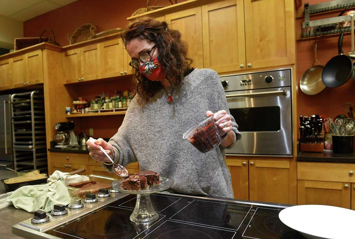 Caroline Barrett tops her spiced chocolate sweet potato cake with chocolate at Different Drummer's Kitchen on Wednesday, Nov. 27, 2020 in Albany, N.Y. (Lori Van Buren/Times Union)