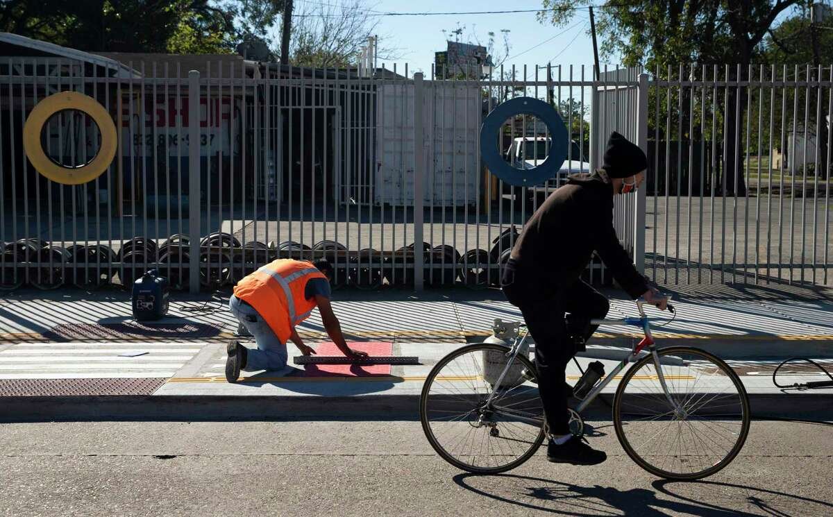 A bicyclist pedals by as workers install a crosswalk on a bike lane near Cavalcade Street and the Interstate 45 frontage road on Nov. 17, 2020, in Houston. Metropolitan Transit Authority is extending the bike lane along Cavalcade Street from Irvington to Elysian as part of a $1.3 million project. This extends the existing bike lane which runs from Airline to Irvington and improves access to the Red Line light rail.