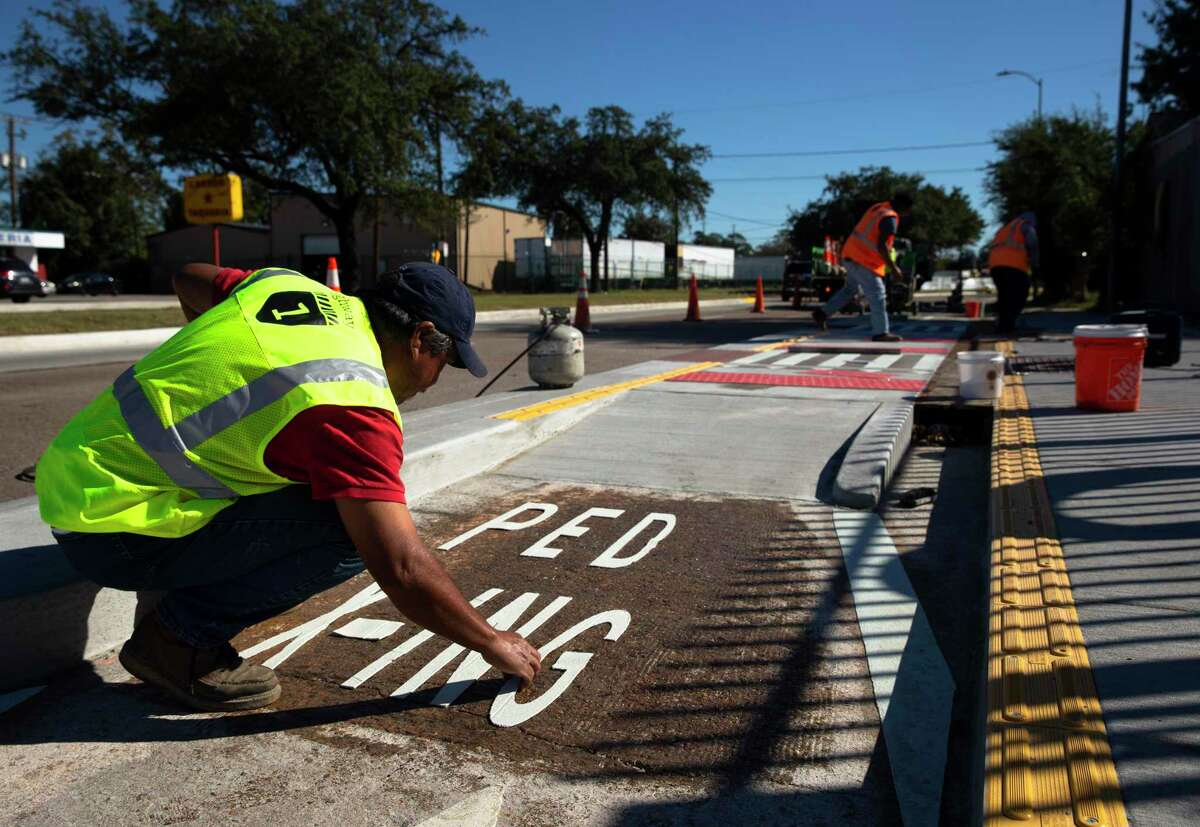 Workers install a crosswalk on a bike lane near Cavalcade Street and the Interstate 45 frontage road on Nov. 17, 2020, in Houston.