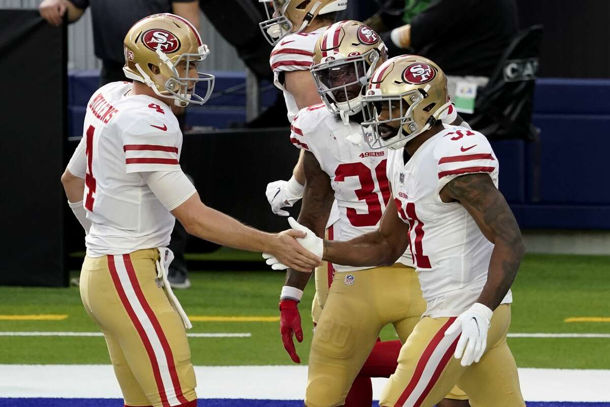 San Francisco 49ers quarterback Nick Mullens, left, congratulates running back Raheem Mostert, right, after Mostert scores during the first half of an NFL football game against the Los Angeles Rams Sunday, Nov. 29, 2020, in Inglewood, Calif. (AP Photo/Alex Gallardo)