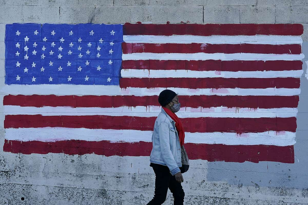 A woman wears a mask while walking past an American flag painted on a wall in San Francisco on Nov. 16.