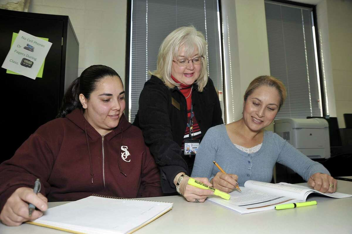 A college instructor, center, helps English as a Second Language students with English grammar lessons in this pre-pandemic photo.