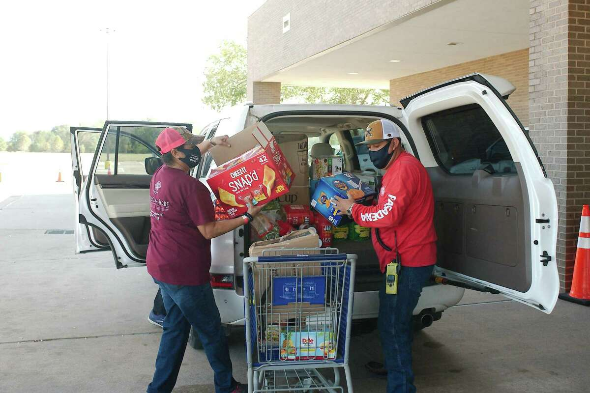 Rachel Rodriguez and Juan Arnada unload food donated by Chevron employees during the 2020 Pasadena Food Drive at the Pasadena Convention Center.
