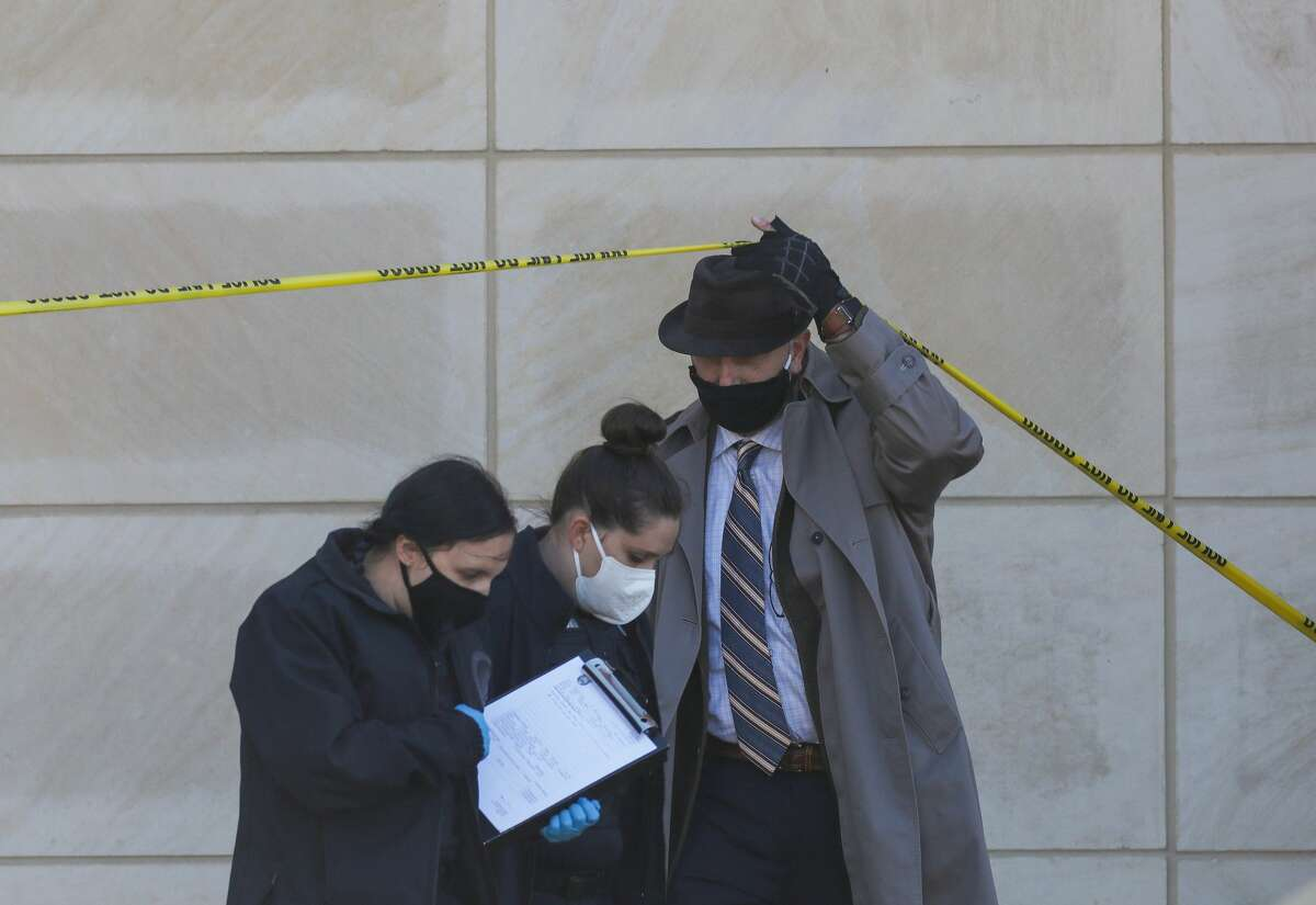 Houston Police officers and homicide detectives investigate the scene where a dead body was found outside the Science and Engineering Classroom Building at the University of Houston on Monday, Nov. 30, 2020, in Houston.