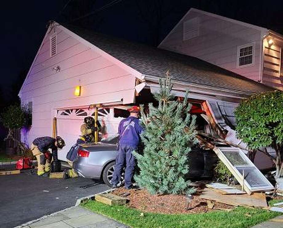 A vehicle slammed into a garage attached to a home in North Stamford. Photo: Contributed / Deputy Fire Chief Matt Palmer / Stamford Fire Department