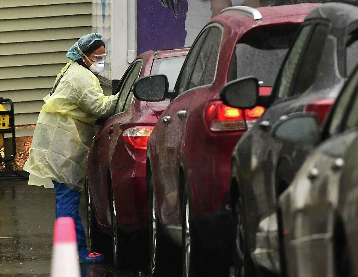 A health care worker takes a sample for a COVID-19 test at a drive-thru testing site at the Whitney Young Health Center on Monday, Nov. 30, 2020 in Albany, N.Y. The site also accepts walk-ins. (Lori Van Buren/Times Union)