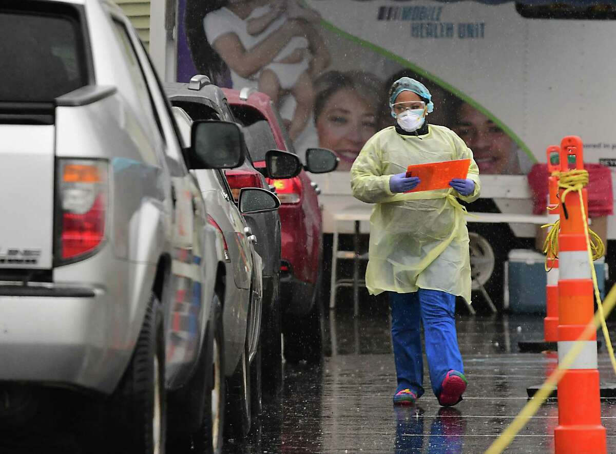 A health care worker brings out paperwork to people in cars for a COVID-19 test at a drive-thru testing site at the Whitney Young Health Center on Monday, Nov. 30, 2020 in Albany, N.Y. The site also accepts walk-ins. (Lori Van Buren/Times Union)