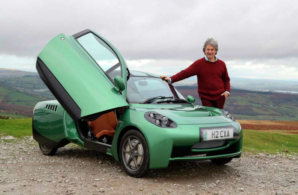 """Hugo Spowers, chief engineer and founder of Riversimple, poses for a photograph with one of his company's hydrogen powered 'Rasa' cars in Llandgynidr, near Brecon in Wales on November 23, 2020. - Hydrogen-powered car manufacturer Riversimple is hoping to steal a march on competitors ahead of Britain's promised """"green revolution"""", which would see petrol-powered cars banned within 10 years. Riversimple is only an ambitious upstart compared to the Asian automotive giants, but is currently the only British manufacturer in the sector with its flagship model, the Rasa. Founder Hugo Spowers is keen to take on the big boys with his self-designed model, whose name derives from the Latin 'tabula rasa', or clean slate. Advanced testing of the Rasa will begin over the next few months, with paying customers including Monmouthshire District Council in south Wales, which has given the go-ahead for a hydrogen refuelling station in the town of Abergavenny. (Photo by GEOFF CADDICK / AFP) (Photo by GEOFF CADDICK/AFP via Getty Images)"""