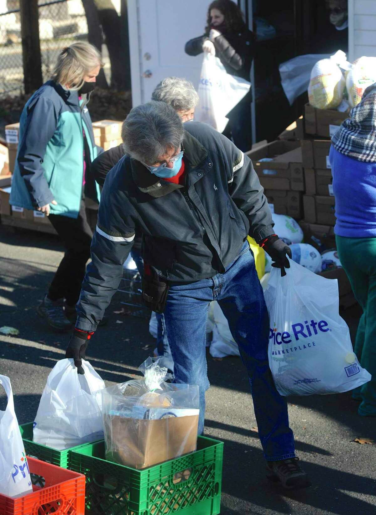 Volunteer Pete Jeffrey, of Danbury, carries bags of food to be distributed by the Daily Bread Food Pantry on Tuesday morning, November 24, 2020, in Danbury, Conn. The pantry distributed about 200 turkeys and other food for Thanksgiving.