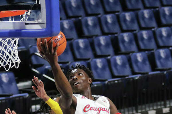 SIUE's Mike Adewunmi (1) drives past two UHSP defenders to score at the rim during the Cougars' win Saturday night in the Billiken Classic at Chaifetz Arena in St. Louis. Adewunmi, a senior, led SIUE in scoring at 13.0 points per game in three games last week at Chaifetz.