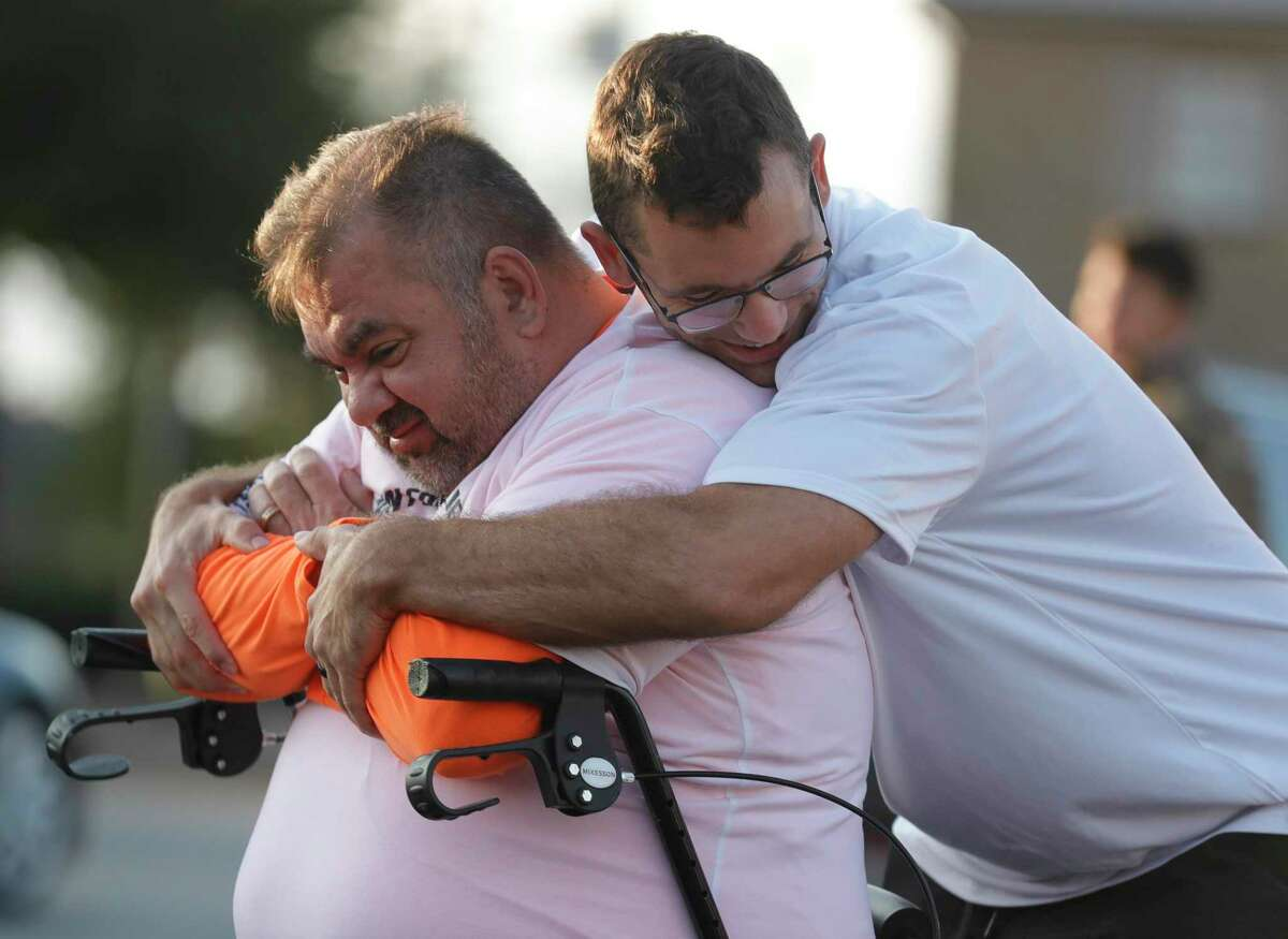 Joe Alvarez, left, gets a hug from his phyiscal trainer Taylor Coibion, owner of The OC Wellness and Fitness, before starting a 5K as he continues to recover from COVID-19 through downtown Conroe, Thursday, Nov. 26, 2020, in Conroe. The Conroe business owner contracted COVID-19 in July and was hospitalized for 32 days on a ventilator and spent time in Houston Methodist Hospital's COVID ward in Katy.