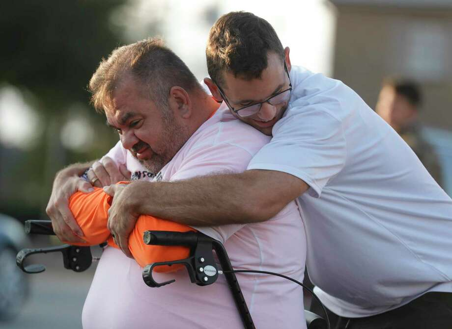 Joe Alvarez, left, gets a hug from his phyiscal trainer Taylor Coibion, owner of The OC Wellness and Fitness, before starting a 5K as he continues to recover from COVID-19 through downtown Conroe, Thursday, Nov. 26, 2020, in Conroe. The Conroe business owner contracted COVID-19 in July and was hospitalized for 32 days on a ventilator and spent time in Houston Methodist Hospital's COVID ward in Katy. Photo: Jason Fochtman, Houston Chronicle / Staff Photographer / 2020 © Houston Chronicle