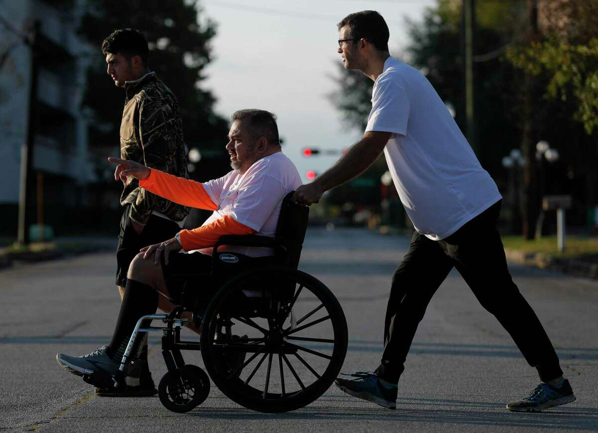 Joe Alvarez points to where he wants to start walking again as he is pushed by his physical trainer Taylor Coibion as he takes a break from walking a 5K through downtown Conroe, Thursday, Nov. 26, 2020, in Conroe. The Conroe business owner contracted COVID-19 in July and was hospitalized for 32 days on a ventilator and spent time in Houston Methodist Hospital's COVID ward in Katy.