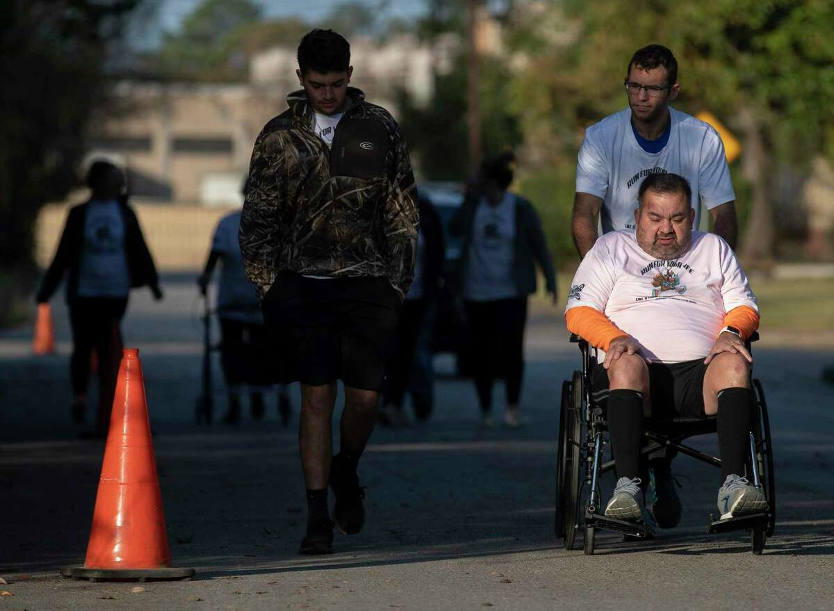 Joe Alvarez is pushed by his physical trainer Taylor Coibion as he takes a break from walking a 5K as he continues to recover from COVID-19 through downtown Conroe, Thursday, Nov. 26, 2020, in Conroe. The Conroe business owner contracted COVID-19 in July and was hospitalized for 32 days on a ventilator and spent time in Houston Methodist Hospital's COVID ward in Katy.