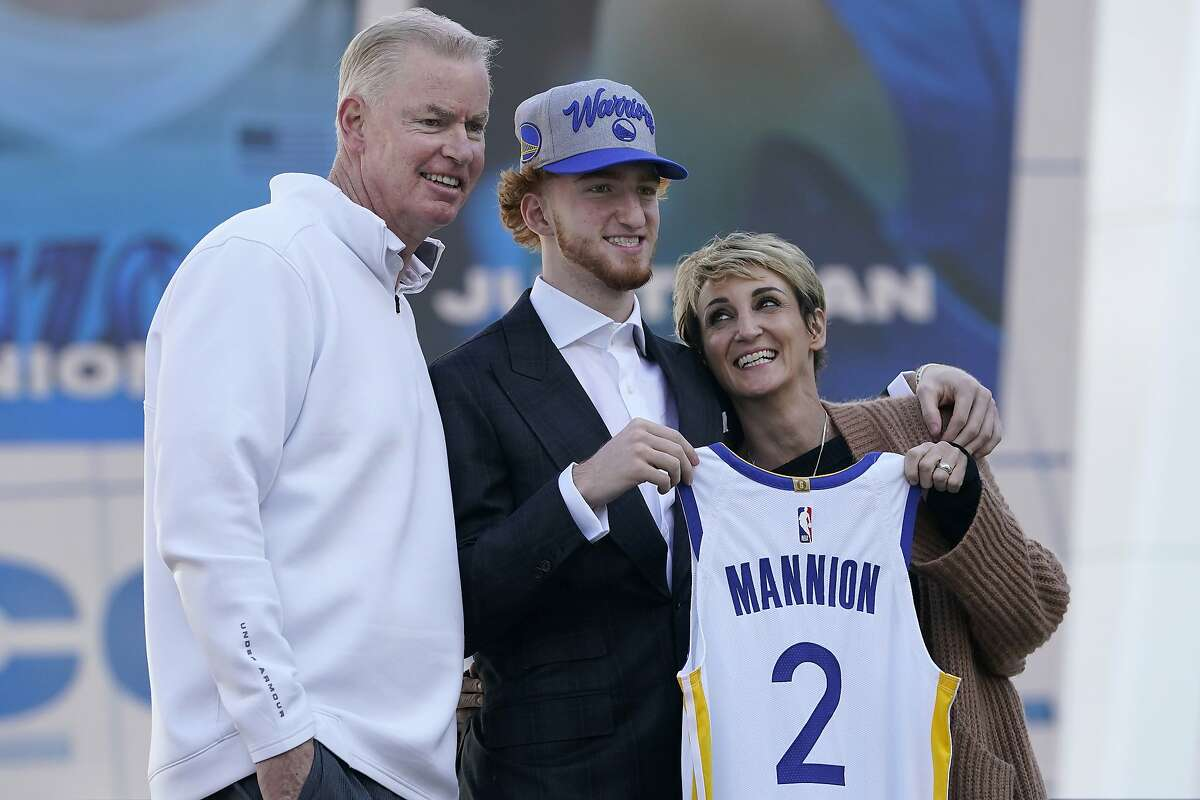 Golden State Warriors draft pick Nico Mannion, center, poses for photos between his father, Pace, left, and mother, Gaia, at a news conference in San Francisco, Thursday, Nov. 19, 2020.