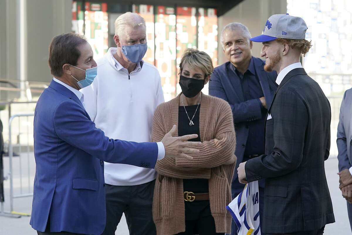 Golden State Warriors owner Joe Lacob, left, greets draft pick Nico Mannion, right, as Mannions father Pace, second from left, and mother, Gaia, center, and agent Bill Duffy watch in San Francisco, Thursday, Nov. 19, 2020.