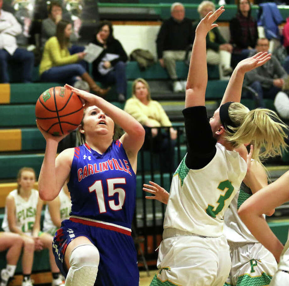 Carlinville's Gracie Reels (15) puts up a shot over Southwestern's Addie Green (3) during a Jan. 8 South Central Conference girls basketball game last season in Piasa. Reels, a first team All-SCC performer as a junior for a 28-4 team, and the Cavaliers were scheduled to open their 2020-21 season Monday night at Carrollton, while Green and the Piasa Birds were to debut at home against Brown County. Monday was supposed to be the first date boys and girls basketball teams could play under a revised winter schedule, but the season has been put on pause indefinitely because of COVID-19. The IHSA board of directors is scheduled to meet Wednesday, and again Dec. 14, with discussion of a possible resumption date among items on the agenda. Photo: Greg Shashack / The Telegraph