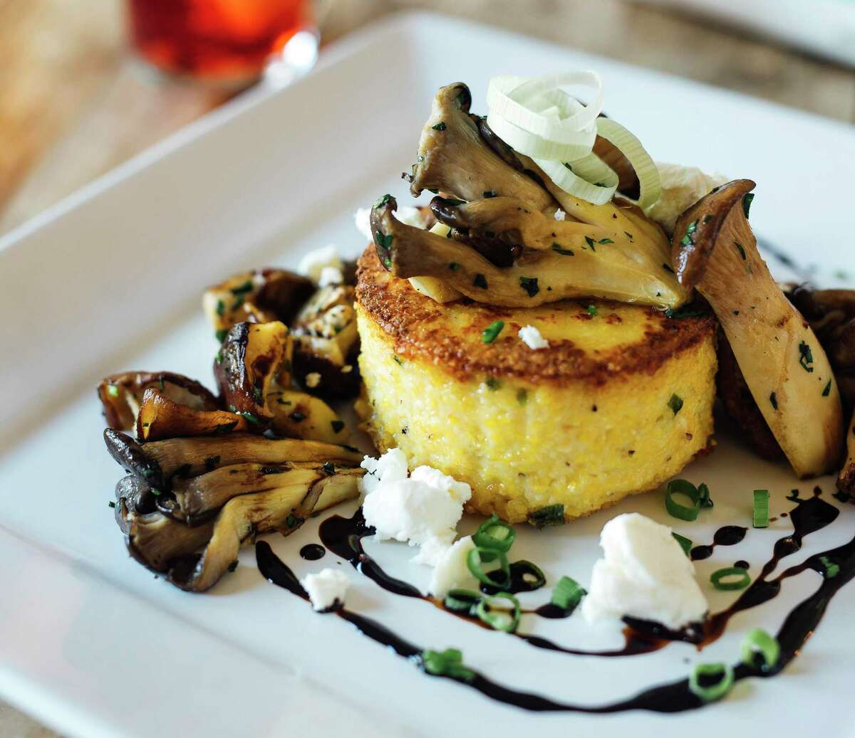 Green onion polenta cake with Texas goat cheese, wild mushrooms and balsamic reduction will be part of the menu at Bar Loretta, a new bar and restaurant concept coming to Southtown in February 2021.