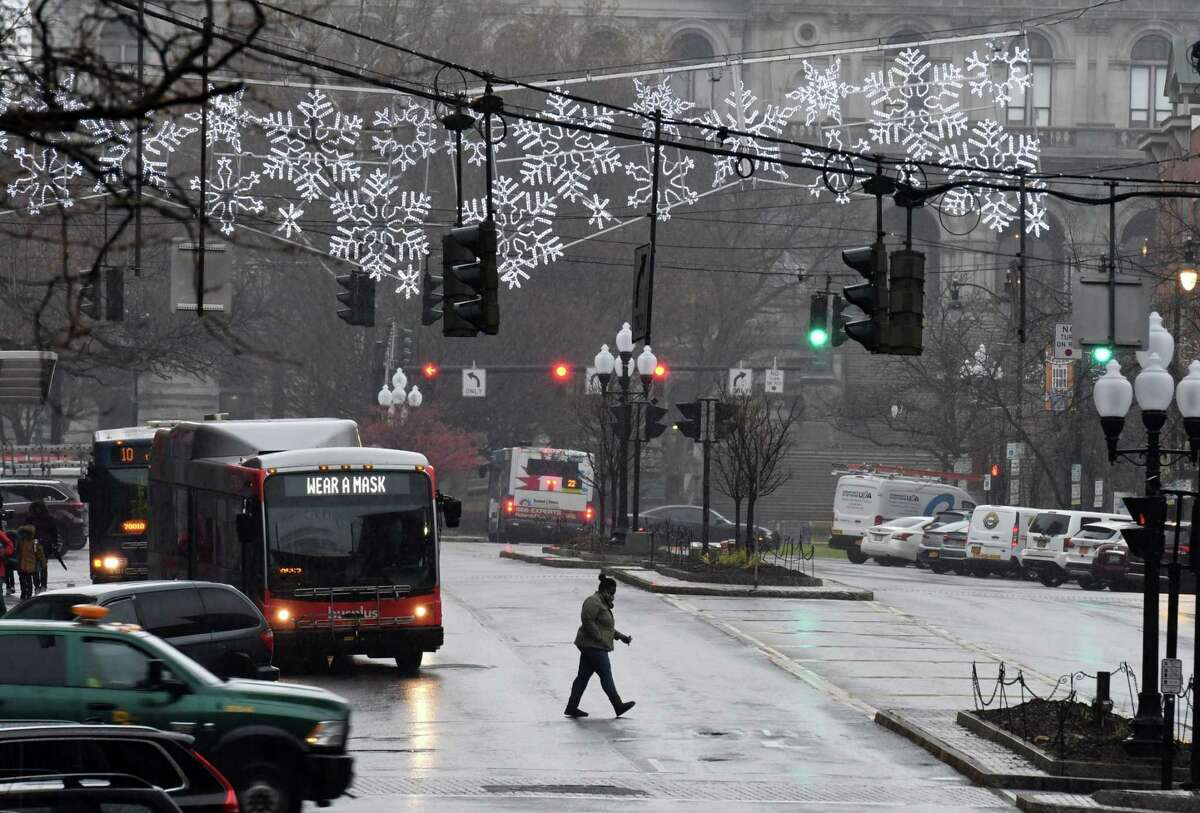 Holiday lights are up on State Street as a sign on a CDTA bus reminds us to wear masks in a effort to help stop the spread of coronavirus on Monday, Nov. 30, 2020, in Albany, N.Y. (Will Waldron/Times Union)