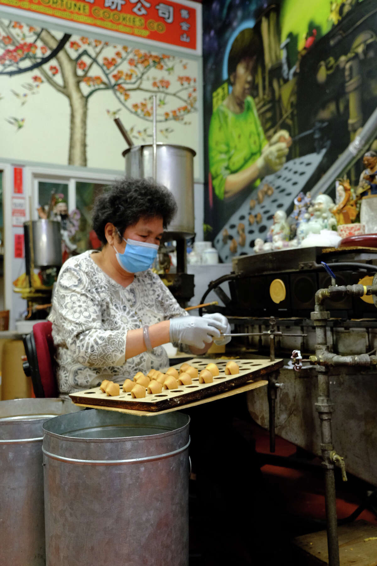 Nancy Tom Chan, owner of the Golden Gate Fortune Cookie Factory, folds fortune cookies on Nov. 8, 2020.