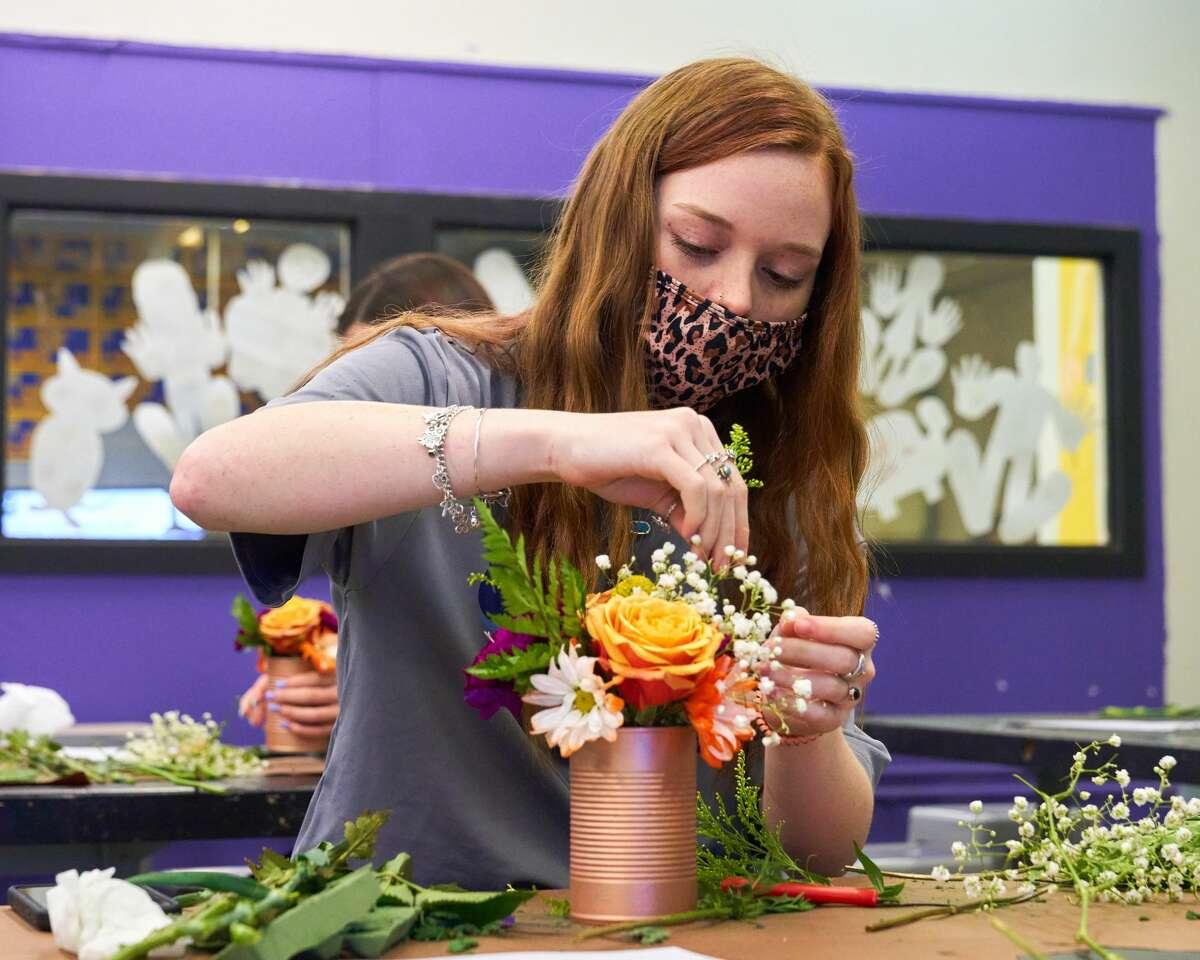 Midland High School students create floral designs using fall seasonal colors.