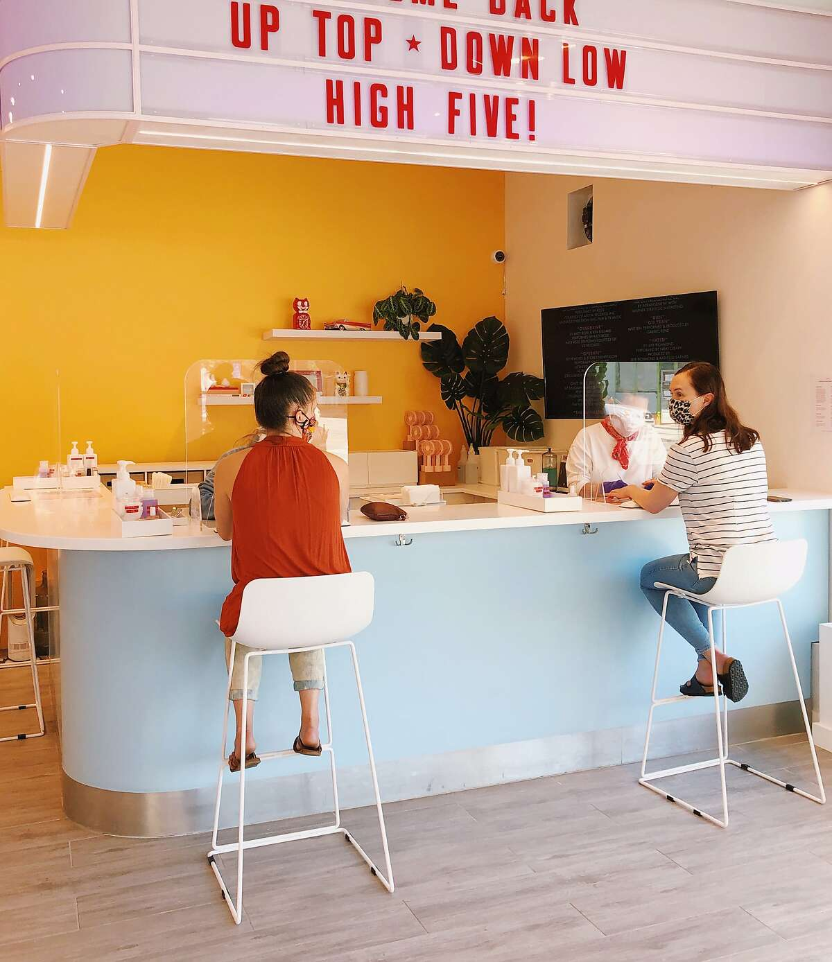 COVID-friendly manicure stations with plexiglass barriers inside High Five nail salon in San Francisco.