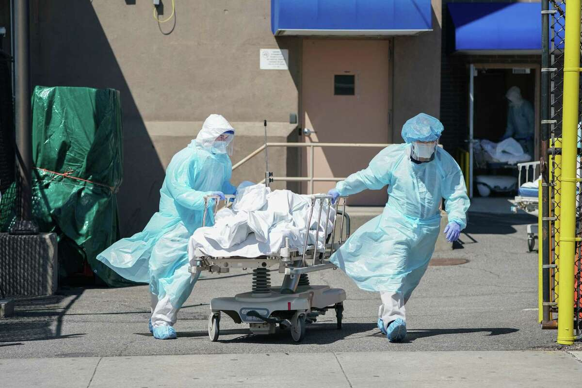 (FILES) In this file photo bodies are moved to a refrigeration truck serving as a temporary morgue at Wyckoff Hospital in the Borough of Brooklyn on April 6, 2020 in New York. - America should prepare for a