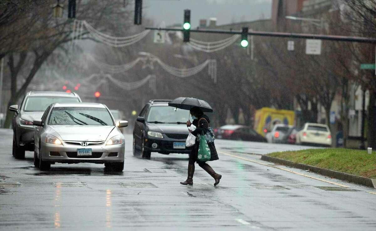 Pedestrians cross Main Street, in Danbury, during the rain on Monday morning.