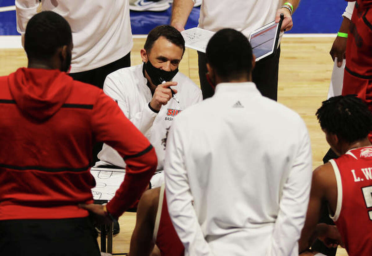 SIUE coach Brian Barone (middle) talks with his team during a timeout in a game against Saint Louis on Wednesday night at Chaifetz Arena in St. Louis.