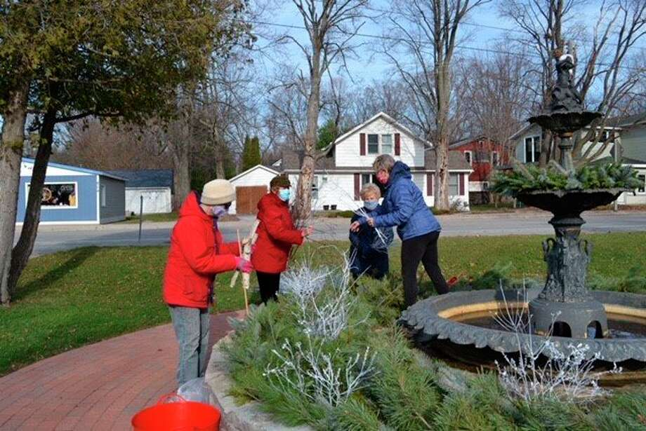 Portage Lake Garden Club Members decorate Onekama's Memorial Fountain. (Courtesy Photo)