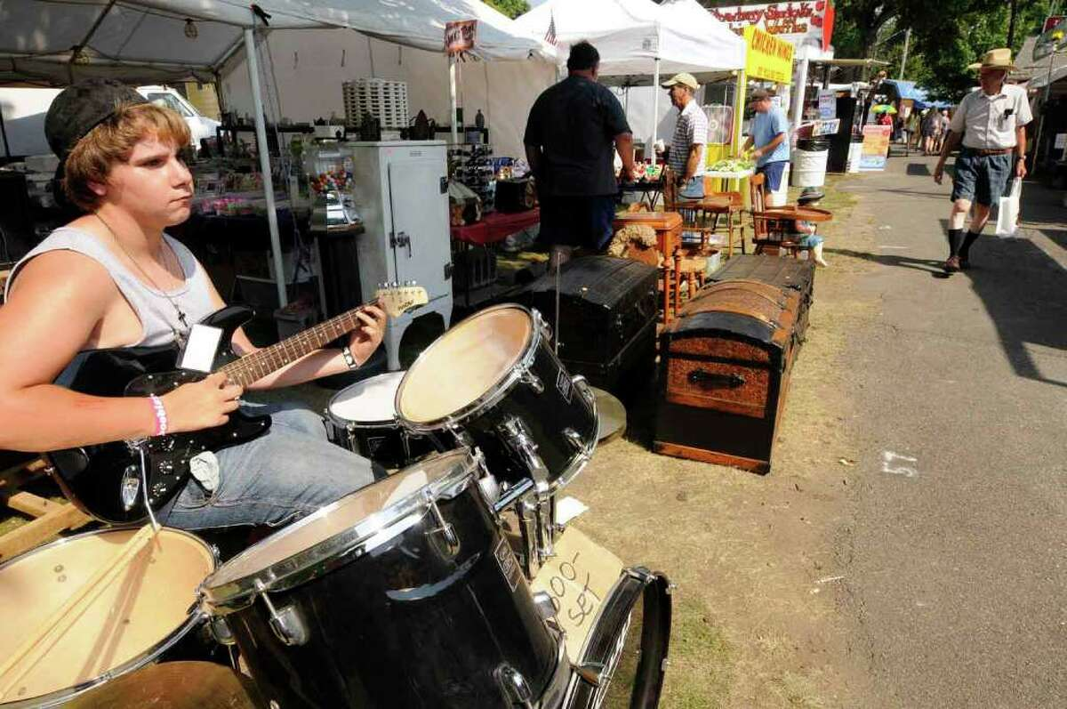 Will Bame, 13, plays a guitar for sale at the Patrick's Junk in His Trunk booth. Bame was working the booth during the Columbia County Fair in Chatham on Thursday, Sept. 2, 2010. ( Michael P. Farrell / Times Union )