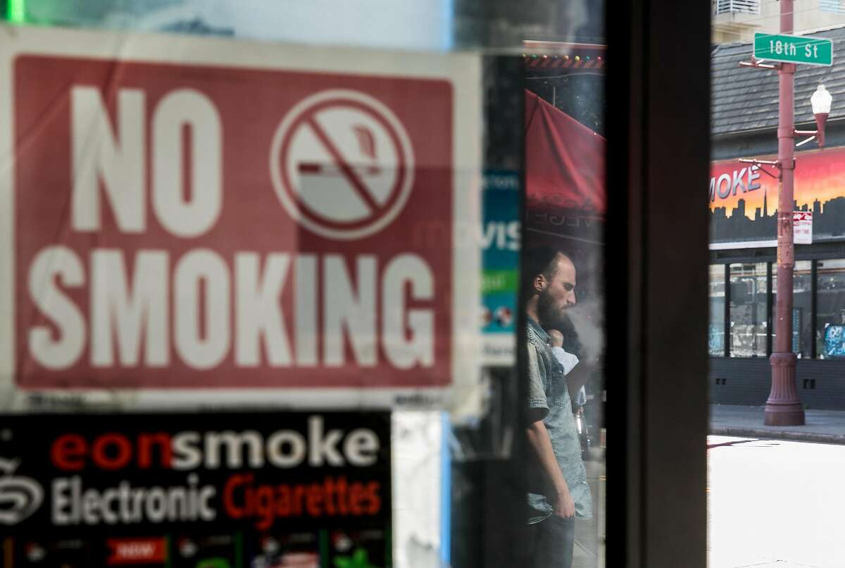 A man smokes an e-cigarette outside of The Town Smoke Shop in the Mission district of San Francisco, Calif. Thursday, March 21, 2019.