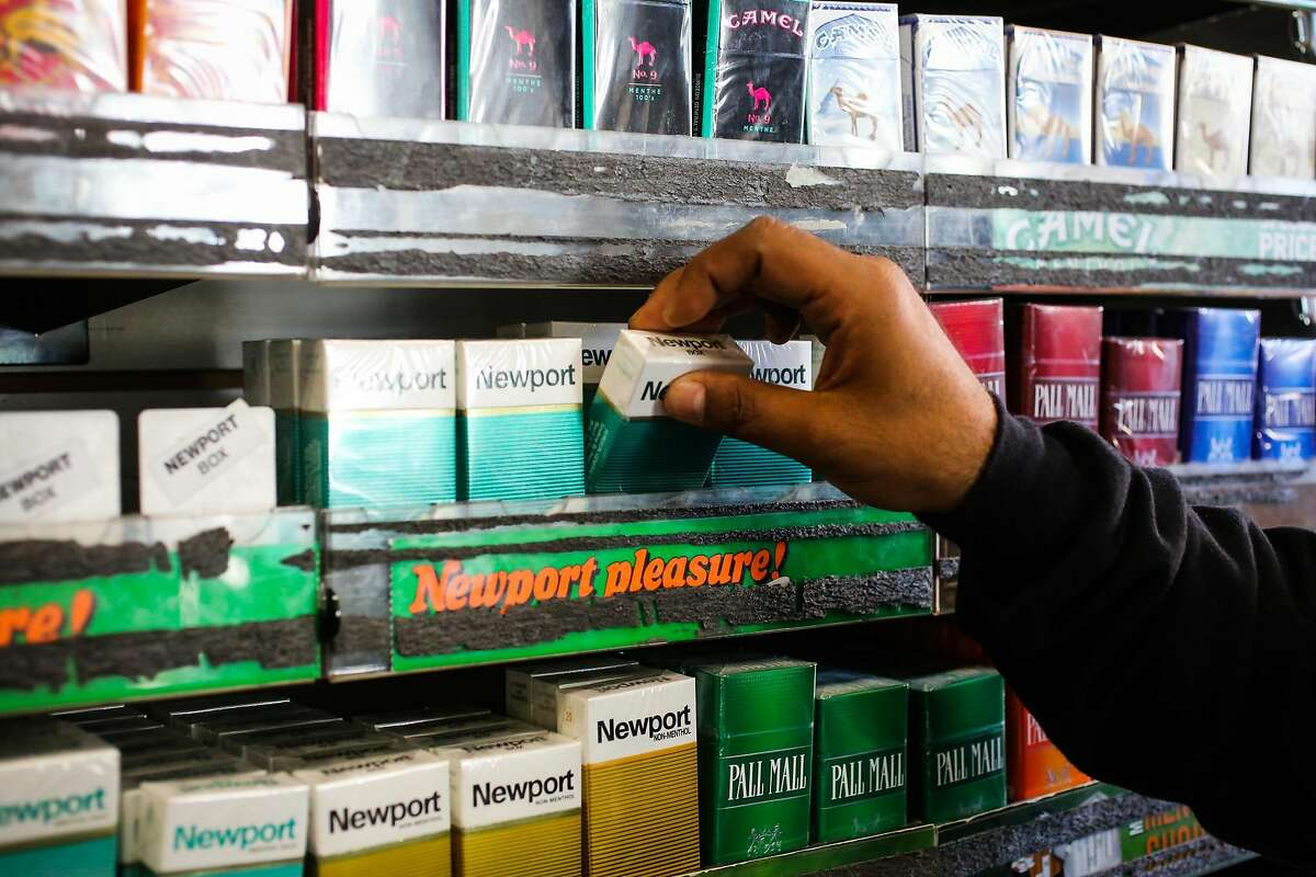 Store employee Majid Abbas grabs menthol cigarettes for a customer at City Smoke and Vape Shop in San Francisco, California, on Sunday, June 11, 2017.